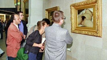 """Des visiteurs regardent """"L'Origine du monde"""" de Gustave Courbet, au Musée d'Orsay à Paris le 26 juin 1995"""