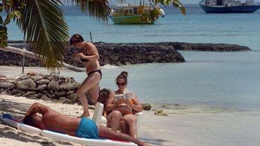 Des touristes sur une plage de l'île de Kurumathi, à l'Ouest de Mahé