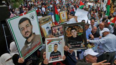Des manifestants brandissent des portraits de Palestiniens détenus par Israël à l'occasion de la journée annuelle des prisonniers, le 17 avril 2018 à Naplouse, dans le nord de la Cisjordanie occupée