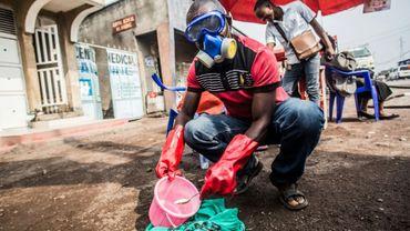 Un agent sanitaire portant un masque et des gants de protection prépare un mélange désinfectant à base de chlore, le 31 juillet 2019 à Goma, en RDC