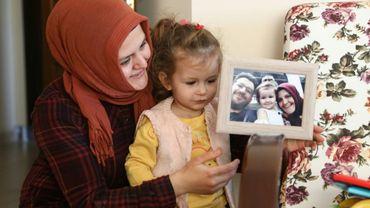 Sümeyye Yilmaz, avec sa fille, montre une photo de famille où l'on voit son mari Mustafa Yilmaz, disparu pendant huit mois, le 21 novembre 2019 à Ankara