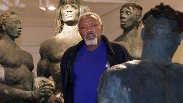 """Le sculpteur sénégalais Ousmane Sow pose près d'une de ses oeuvres, le 01 décembre 1999, dans la salle d'exposition du """"Rectangle"""" à Lyon."""