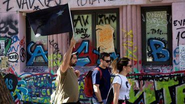 Des touristes visitent le centre de Santiago, le 10 janvier 2020, dont les murs sont recouverts de graffitis et d'inscriptions qui expriment la crise sociale que traverse le pays