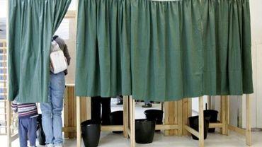 Une personne vote dans un isoloir