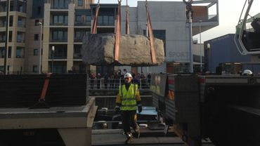 Cette pierre de 12 tonnes et demi est arrivée par Péniche. Elle a ensuite été hissée sur un camion par une grue avant d'être posée sur la place de Molenbeek.