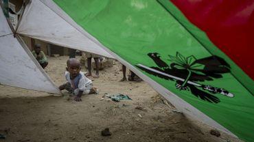 Un enfant joue dans une tente faite avec le drapeau du parti présidentiel CNDD-FDD en juillet 2015 à Bujumbura.