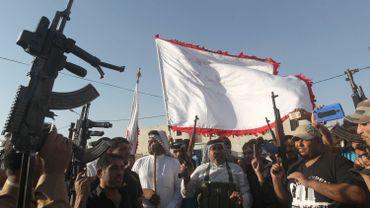Des volontaires brandissent les armes qui leur ont été fournies par l'armée irakienne, pour contrer l'avancée des djihadistes sunnistes