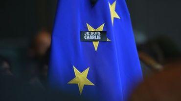 """Un badge """"Je suis Charlie"""" sur un drapeau de l'union européenne, au Parlement européen à Bruwelles, le 8 janvier 2015, au lendemain des attentats terroristes qui ont touché à Paris la rédaction du journal satirique et fait 12 morts"""