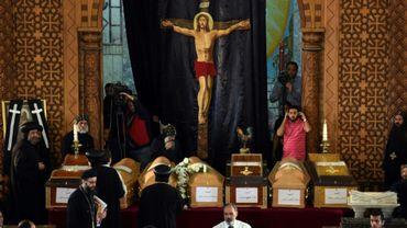 Des prêtres coptes se tiennent près des cercueils des victimes de l'attentat de l'église Saint-Marc d'Alexandrie, le 10 avril 2017 au monastère de Mar Mina dans la ville de Borg El-Arab