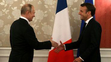 Le président français Emmanuel Macron (D) serre la main de son homologue russe Vladimir Poutine, le 28 juin 2019 lors du sommet du G20 à Osaka, dans le sud du Japon