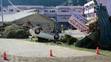 Une voiture sur le toit et des bâtiments endommagés après le passage du typhon Lionrock, le 1er septembre 2016 à Iwaizumi, dans la préfecture d'Iwate, au Japon
