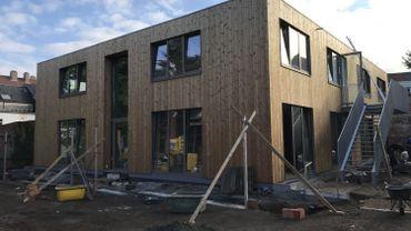 Le bâtiment à ossature bois est isolé avec des ballots de paille compressés recouverts d'argile