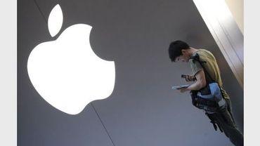 Un client utilise sa tablette numérique iPad à l'extérieur d'une boutique Apple à Shanghaï le 28 juin 2012