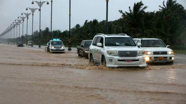 Photo prise le 25 mai 2018 montrant des voitures roulant sur une route inondée dans la ville omanaise de Salalah, alors que le sultanat attend le cyclone Mekunu