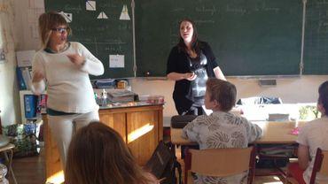 Dans la classe, l'institutrice se fait toujours aidée par un autre professeur usant de la langue des signes.