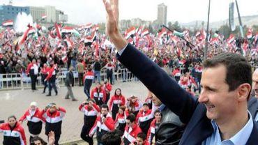 Bachar al-Assad salue les participants à une manifestation de soutien au régime, le 11 janvier 2012 à Damas