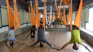 Le yoga aérien se pratique dans un hamac suspendu au plafond. Ici un exemple à Ahmedabad, en Inde, le 18 juin 2015.