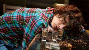 Drunk man slumped on bar asleep