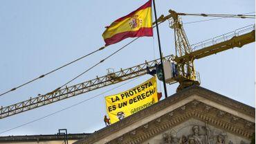 """""""Manifester est un droit."""" Des militants de Greenpeace déploient une banderole à Madrid ce 30 juin 2015 à quelques heures de l'entrée en vigueur de la polémique loi de sécurité citoyenne, appelée """"ley mordaza"""" (loi bâillon)."""