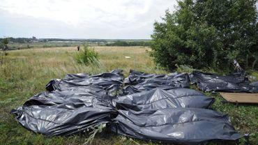 Des corps de victimes du crash qui ont été retrouvés sont alignés au bord de la route en attendant leur enlèvement.