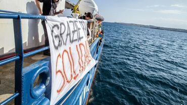 """Des militants d'aide aux migrants à bord du """"Sea Watch 3"""", qui a jeté l'ancre près de Syracuse (est de la Sicile), déploient une banderole en italien """"Merci pour la solidarité"""", le 26 janvier 2019."""