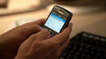 Un homme regarde ses e-mails sur son Blackberry à Washington, le 23 novembre 2010