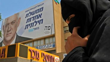 Une femme bédouine près d'une affiche électorale de Benny Gantz, le 15 septembre 2019 à Beer-Sheva (sud d'Israël)