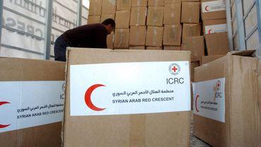 Un assistant du Croissant rouge décharge du matériel d'aide, à la ville de Deraa, en Syrie