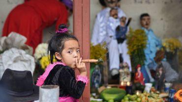 Une fillette de trois ans fume un cigare lors des célébrations du saint Simon à San Andres Itzapa, au Guatemala, le 28 octobre 2019. Des milliers de personnes pensent que le saint aide les gens à trouver du travail, à résoudre leurs problèmes familiaux et à soigner les maladies.