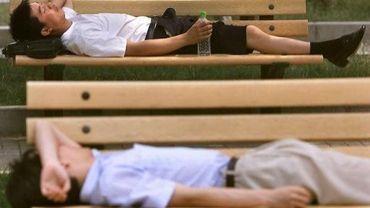 Deux jeunes gens font la sieste sur des bancs