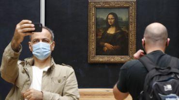 """Un visiteur du Louvres devant """"La Joconde"""" de Léonard de Vinci au Louvre le 6 juillet 2020, jour de la réouverture du musée."""