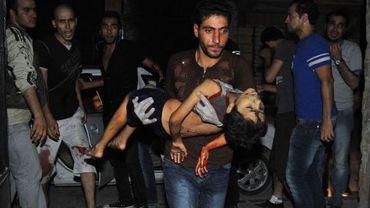 Un homme porte un enfant blessé à Alep