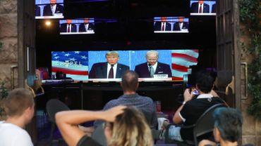 Les gens regardent la diffusion du premier débat entre le président Donald Trump et le candidat démocrate à la présidence Joe Biden à l'Abbaye, avec des sièges extérieurs distants, le 29 septembre 2020 à West Hollywood, Californie.
