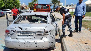 Un policier libyen inspecte une voiture après la chute d'une roquette près de l'aéroport de Mitiga, à Tripoli, le 24 août 2019