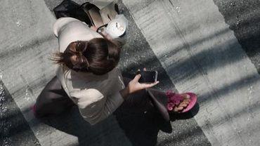 Une femme regarde son téléphone tout en traversant la rue