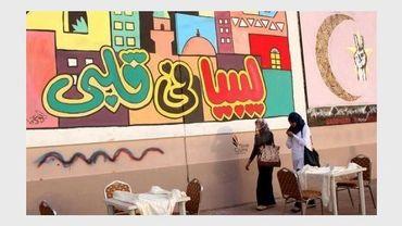 """Des Libyennes passent devant une fresque sur laquelle on peut lire: """"La Libye dans nos coeurs"""", le 23 octobre à Tripoli"""