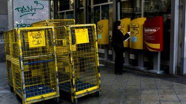 Une femme dépose des lettres dans une boîte aux lettres postale, le 17 mars 2017 à Athènes, en Grèce