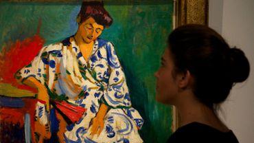 """Une assistante de galerie pose devant le tableau """"Madame Matisse au Kimono"""" de l'artiste français André Derain à la maison de vente aux enchères Christie's à Londres le 4 avril 2013"""