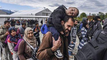 Illustration : Des réfugiés font la file pour embarquer dans un train. Ils viennent de traverser la frontière entre la Macédoine et la Grèce