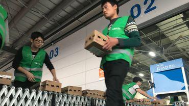 Des travailleurs chargent des camions avec des colis devant un entrepôt de Cainiao Smart Logistics dans le Xiasha Park de Hangzhou (Chine), le jour de la fête des célibataires, le 11 novembre 2019