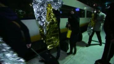 Des passagers, drapés dans des couvertures de survie, descendent de l'Eurostar à Lille.