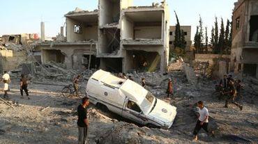 Des Syriens devant un véhicule de la protection civile immobilisé dans un trou causé par une frappe aérienne ville de Douma, tenue par les rebelles, au nord-est de la capitale Damas, le 16 juin 2015