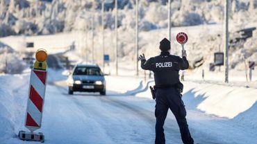 Un policier fédéral allemand arrête un véhicule pour un contrôle à un poste frontière avec l'Autriche le 14 février 2021 près de Zinnwald.