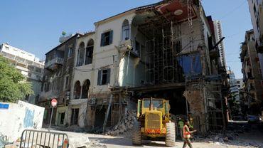 Des ouvriers enlèvent les décombres sous un bâtiment partiellement détruit par l'explosion dans le port de Beyrouth, le 26 août 2020 au Liban