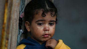 Une enfant se tient à l'intérieur d'une tente dans un camp de fortune à côté du camp de Moria sur l'île de Lesbos le 30 novembre 2019