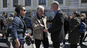 """Costas-Gavras (au centre) sur le tournage à Athènes de son prochain film, une adaptation du livre """"Conversations entre adultes, dans les coulisses de l'Europe"""" de Yanis Varoufakis"""