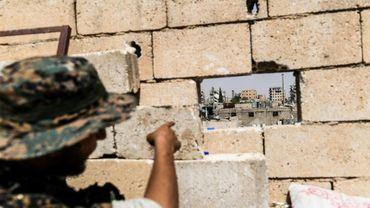 Un membre des Forces démocratiques syriennes (FDS) montre la position des snipers du groupe jihadiste Etat islamique (EI)