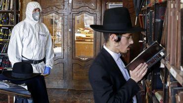 Un policier israélien en tenue de protection vérifie que les mesures de distanciation sont respectées dans une yeshiva (centre d'étude de la Torah) à Bnei Brak- Israel