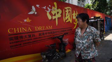 """Une femme regarde une bannière sur le """"China Dream"""" , la vision du président chinois Xi Jinping pour l'avenir de la Chine ,"""