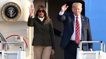 Le président américain Donald Trump et son épouse Melania Trump saluent à leur arrivée à l'aéroport de Prestwick, au sud de Glasgow, le 13 juillet 2018 en Ecosse